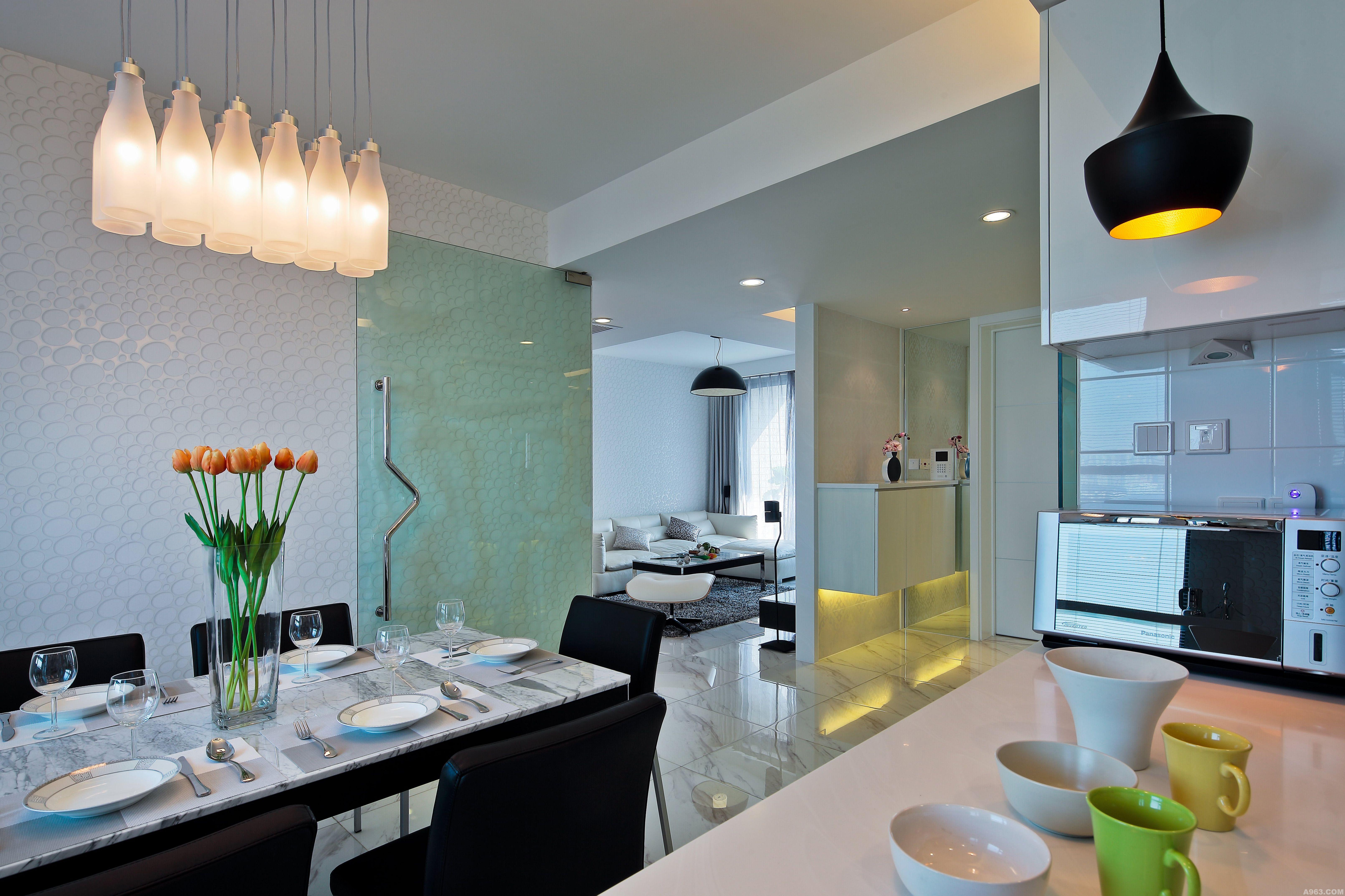此宅是位于上海著名徐家汇商圈的高档楼盘内一套新婚夫妇的结婚用房,该楼盘的当时房价在上海是属于超高单价楼盘。 设计师拆除了餐厅与厨房之间的隔墙,在视觉上扩大了餐厅与厨房的各自空间,并使阳光提亮了这个餐厅与厨房的共享空间。拆除了主卧房与主卫间之间的隔墙, 使阳光可以从二个方向照射进主卧房。增建了玄关与客厅之间的隔墙,使之既遮挡了进户后视线上的一览无遗,又自然形成了客厅的电视墙。 圈形图案无论是出现在玄关墙面的白镜和餐厅的玻璃门片上;还是出现在客厅、餐厅墙面壁纸和主卫间的玻璃隔断上,设计师在这套住宅内使用了不同